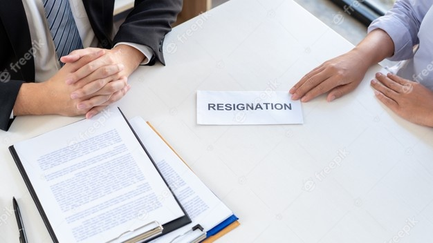 Business man handling out resignation letter to his employer on the desk of the boss