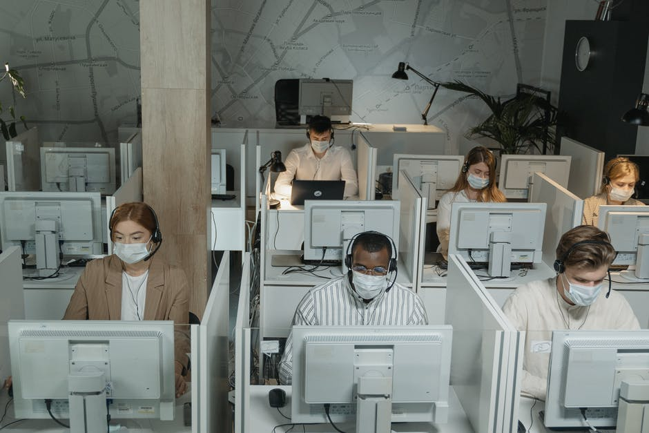 Men and women office worker wearing facemask working separate office cubicles