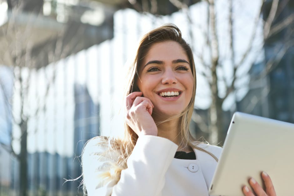 Career woman answer the call smiling wearing white blouse and holding and ipad